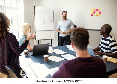 Smiling manager giving a creative whiteboard presentation to a diverse group of staff sitting around a table in an office boardroom