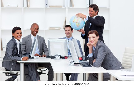 Smiling manager holding a terrestrial globe with his team working at computers. Business concept.