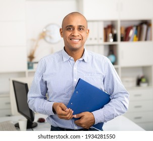 Smiling manager in office standing near workplace. Light tone photo