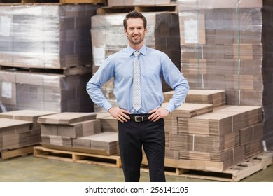 Smiling manager placing his hands on his hips in a large warehouse