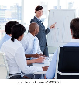 Smiling manager reporting sales figures to her team at a meeting