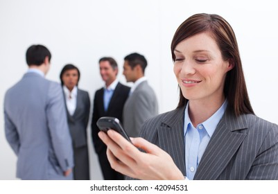 Smiling manager sending a text with a mobile phone with his team in the background