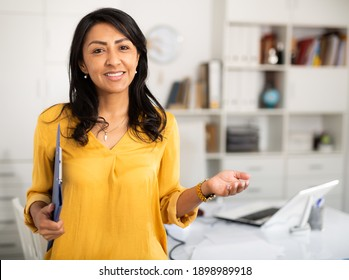 Smiling manager woman in office standing near workplace. Light tone photo