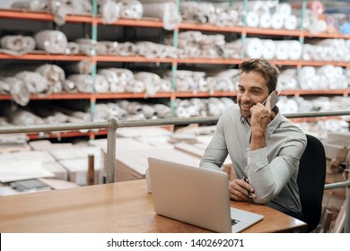Smiling manager working at his desk in a carpet warehouse and talking on a cellphone with shelves of stock in the background