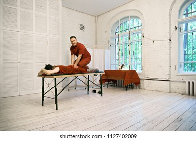 Smiling manual therapist standing on caucasian male patient back. Horizontal shot