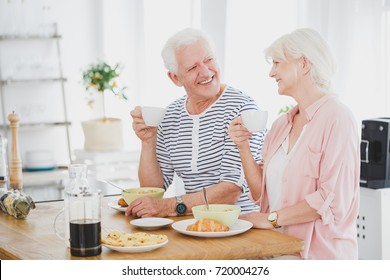 Smiling marriage of elders eat breakfast at wooden table and drink coffee in dining room