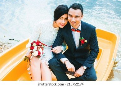 smiling married couple in yellow boat on water