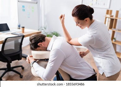 Smiling masseuse doing back massage with elbow for businessman in office on blurred background