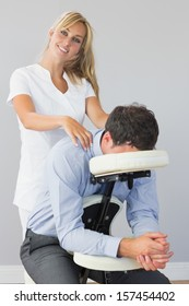 Smiling masseuse treating clients neck in massage chair in bright room