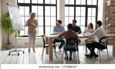 Smiling mature 60 year old businesswoman flip charts presentation new project in boardroom at company meeting. Happy coach auditor speaks with diverse colleagues about business using board and graphs.
