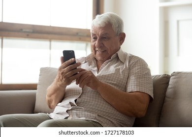 Smiling mature 80s man sit on sofa in living room texting messaging on modern smartphone gadget, happy senior 70s grandfather rest on couch at home browse internet on cellphone, technology concept