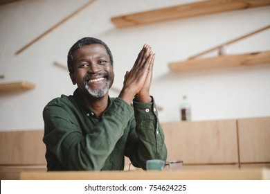 smiling mature african american man sitting in cafe