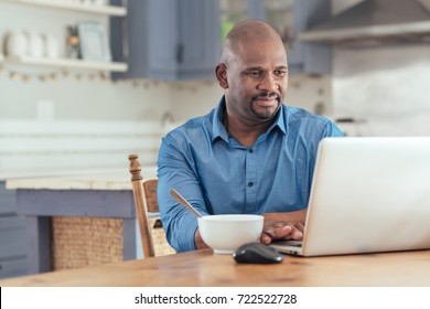 Smiling mature African man sitting at his kitchen table eating breakfast and browsing online with a laptop