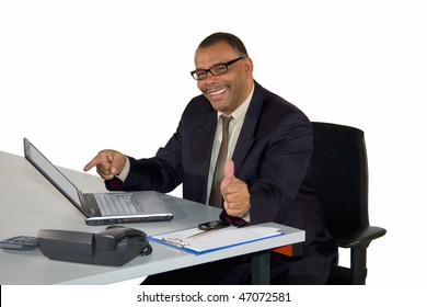 a smiling mature African-American businessman pointing at his laptop and posing with the thumbs up, isolated on white background