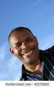a smiling mature African-American man photographed in the summer sun with blue sky and clouds in the background