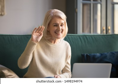 Smiling mature beautiful Caucasian woman sit on couch wave talk on video call on laptop, happy senior retired female or elderly grandmother have pleasant conversation use computer, new technologies