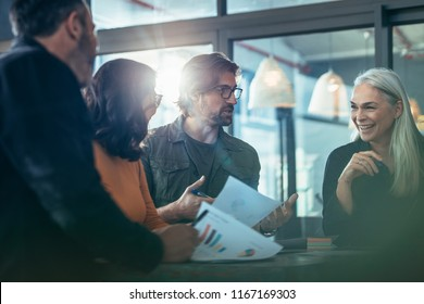 Smiling mature business woman talking with colleagues during meeting. Group of people standing around a table and discussing work.