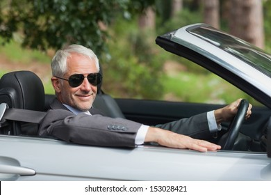 Smiling mature businessman driving classy cabriolet on sunny day