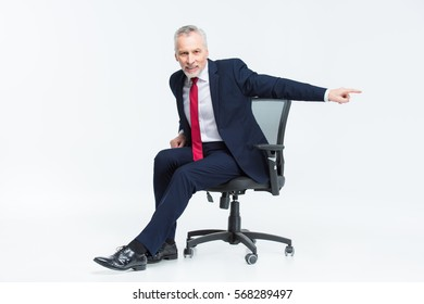 Smiling mature businessman in office chair pointing with his finger isolated on white