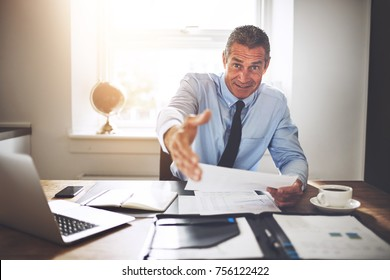 Smiling mature businessman reaching out for a handshake while sitting at his desk in an office holding paperwork