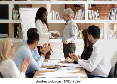 Smiling mature businessman shake hand of young african American employee congratulate with success or promotion, male boss handshake greeting black female worker with business achievement