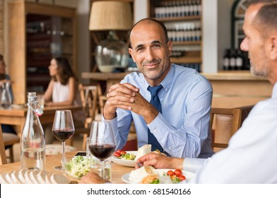 Smiling mature businessman sitting at cafe with partner enjoying meal. Portrait of senior businessman in restaurant looking at camera. Multiethnic man having an informal meeting at restaurant.