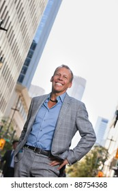 Smiling mature businessman standing with buildings in background