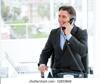 Smiling mature businessman talking on phone sitting at his desk