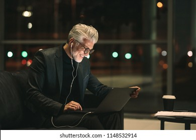 Smiling mature businessman working late on laptop in office lobby. Corporate professional looking at laptop and smiling.