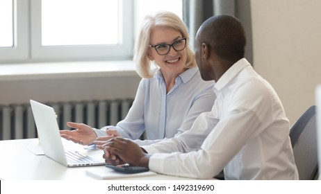 Smiling mature businesswoman coach training African American employee, helping with corporate software, using laptop, senior manager consulting client, colleagues working together, horizontal photo