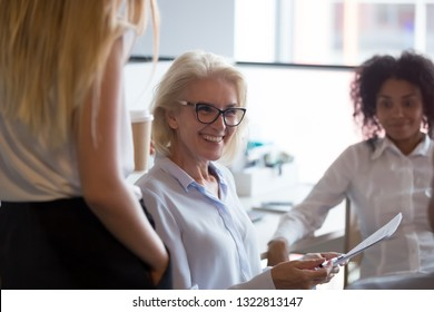 Smiling mature businesswoman holding business briefing with multiracial employees, aged business coach listening colleague ideas, successful negotiations with business partners, close up
