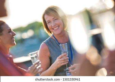 Smiling mature businesswoman talking with colleagues during success party on rooftop