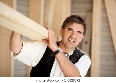 Smiling mature carpenter carrying a large wood plank on his shoulder