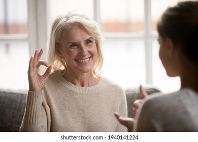 Smiling mature Caucasian 60s woman mother talk communicate with grownup daughter using sign language. Happy elderly female make hand gesture have session with speech therapist or tutor.