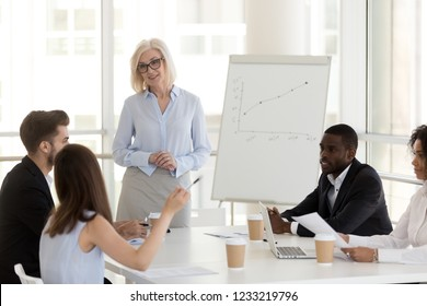 Smiling mature coach mentor communicating with team interns at business meeting, friendly aged female boss leader talking to diverse employees group discussing working together during training class