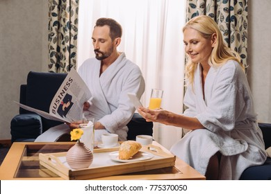 smiling mature couple in bathrobes holding newspaper and smartphone while having breakfast in hotel room