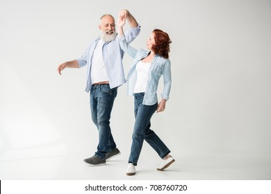 smiling mature couple dancing and holding hands, isolated on white