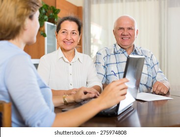 Smiling mature couple discussing for agent or employee of  company at home