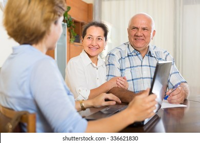 Smiling mature couple discussing for realtor at home