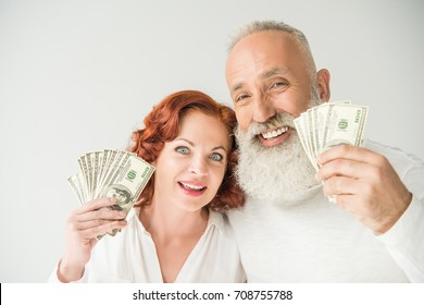 smiling mature couple with dollar banknotes, isolated on white