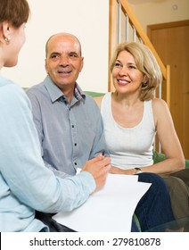 Smiling mature couple filling questionnaire for employee in the living room
