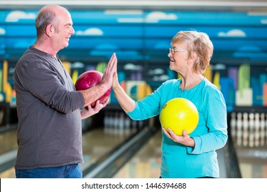 Smiling mature couple holding bowling ball giving high-five
