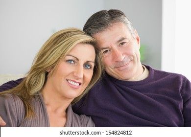 Smiling mature couple looking at camera in a living room