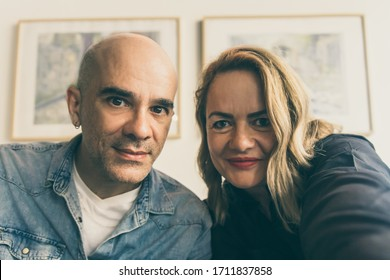 Smiling mature couple posing for self portrait. Cheerful middle aged people looking at camera. View from camera. Self portrait concept