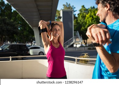 Smiling mature couple stretching after exercise outdoors on city street. Happy fitness woman doing stretching Healthy people looking at each other while doing morning routine exercise.