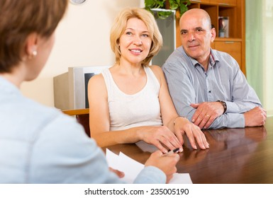 Smiling mature couple  talking with employee at office