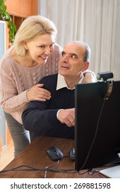 Smiling mature couple using PC for video calls at home