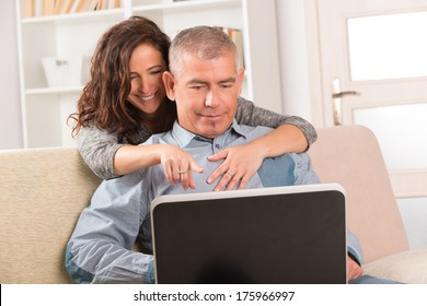 Smiling mature couple using their laptop together on the sofa at home