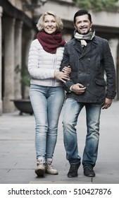 Smiling mature couple walking in city at autumn day