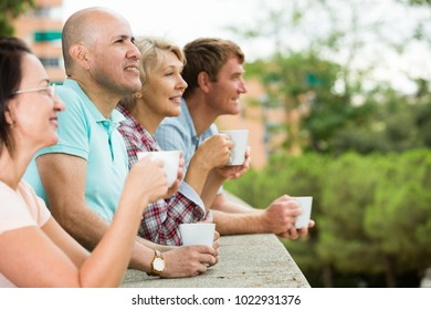 Smiling mature couples walking and drinking coffee on holiday